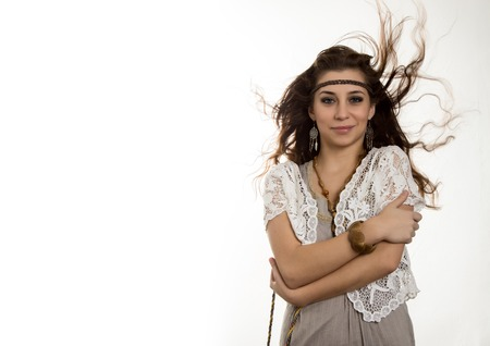 Young beautiful hippie boho woman with fluttering hair having fun poses on a white background. free space for text Standard-Bild - 124446959