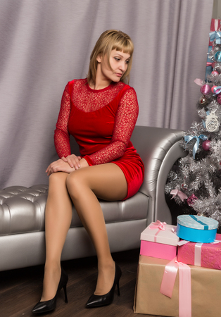 beautiful young blonde woman in a red dress sitting on couch with Christmas decorations Standard-Bild - 124446967