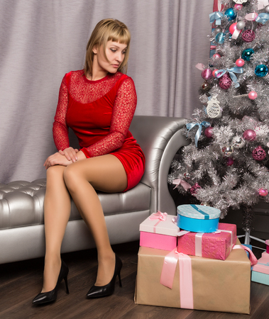 beautiful young blonde woman in a red dress sitting on couch with Christmas decorations Standard-Bild - 124446969