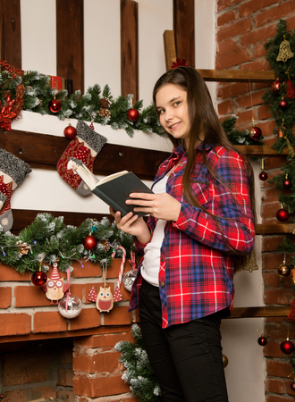 teenag girl reading a book near the fireplace with Christmas decorations Standard-Bild - 124446972