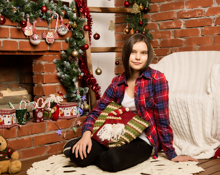 teenag girl sitting near the fireplace with Christmas decorations and toys Standard-Bild - 124446973