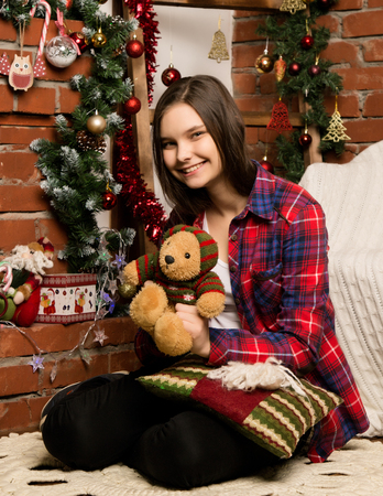teenag girl sitting near the fireplace with Christmas decorations and toys Standard-Bild - 124450360