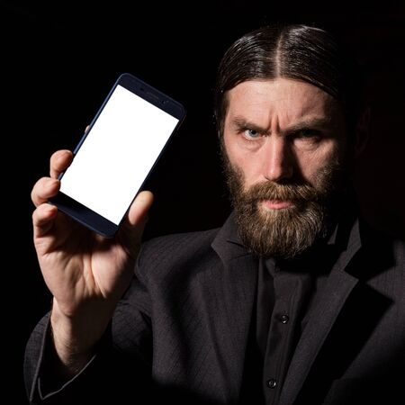 Old believer senior priest with a smartphone, bearded old man is calling on a dark background Stock Photo
