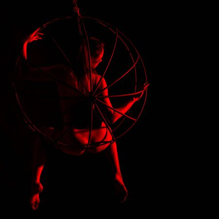 silhouette of sexy woman in red light on a dark background. leggy woman in a bodysuit with metal rings. free space for text