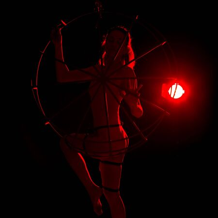 silhouette of sexy woman in red light on a dark background. leggy woman in a bodysuit with metal rings Stock Photo