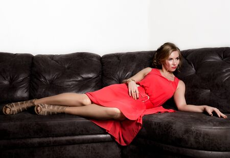 Portrait of beautiful young women in a coral dress resting on sofa