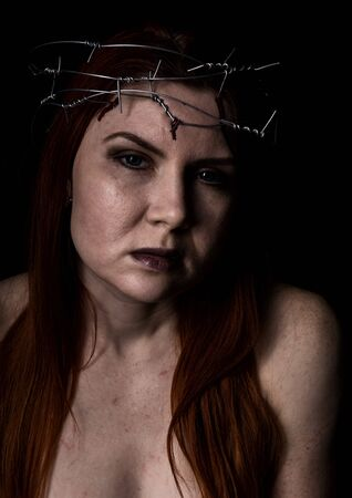 tormented beautiful woman with a wreath of barbed wire on the head on a dark background
