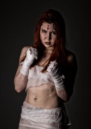 young redhead female fighter after the fight in a dark. girls in martial arts. bloody bandages with fists Imagens