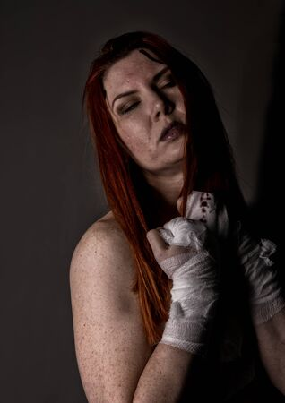 young redhead female fighter after the fight in a dark. girls in martial arts. bloody bandages with fists Stock fotó