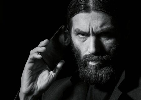 strange bearded senior priest with a smartphone, bearded old man is calling on a dark background. black and white