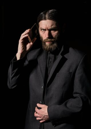 strange bearded senior priest with a smartphone, bearded old man is calling on a dark background