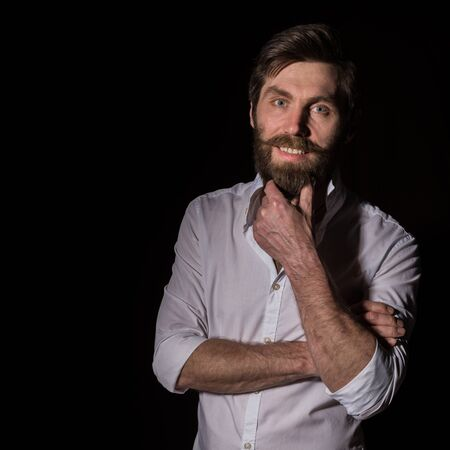 Portrait handsome bearded man, sexy guy on a dark background. free space for text