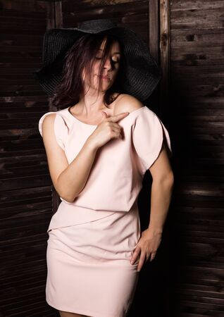 Fashionable woman posing in wide-brimmed black hat. Woman in elegant outfit. Woman fashionable brunette stands on a wooden background.