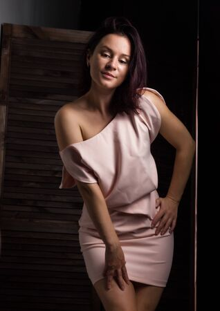 Fashionable woman posing with bare shoulder. Woman in elegant outfit. Woman fashionable brunette stands on a wooden background.