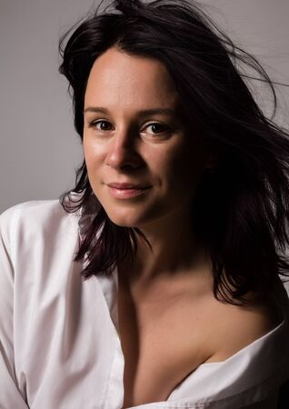 Fashionable woman in a mans white shirt with bare shoulder on a gray background