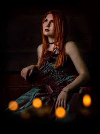 redhaired woman in a retro dress with candles on black background