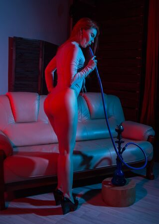 seductive redhead woman sitting on a sofa and smokes hookah in red blue tones