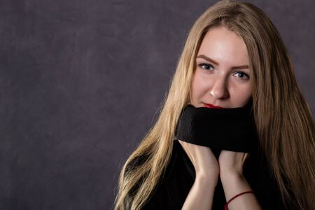 mysterious pretty blonde woman wearing black knitted sweater. Melancholy and autumn concept. on a gray background