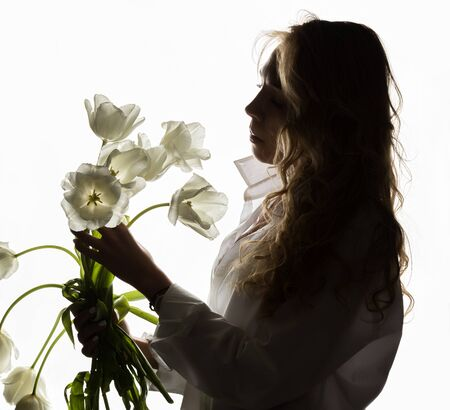 silhouette of beautiful curly girl with spring flowers tulips on a white background