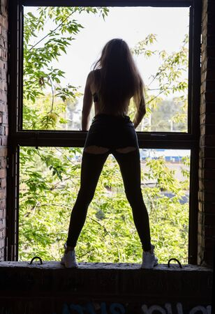 silhouette of slender girl on the background of a large window