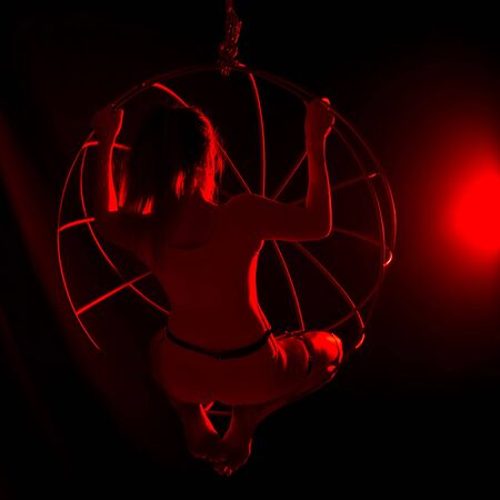 silhouette of sexy female dancer in red light on a dark background. leggy woman in a bodysuit with metal rings. night club concepte Standard-Bild