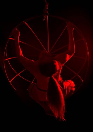 silhouette of sexy woman in red light on a dark background. leggy woman in a bodysuit with metal rings Standard-Bild
