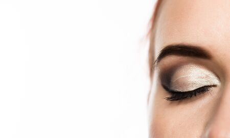 Close-up womans eye with professional makeup smokey eye, on a white background. free space for text