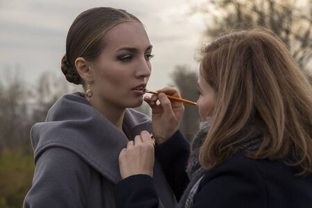 makeup artist makes make up for beautiful model outdoor. paints lips with a brush