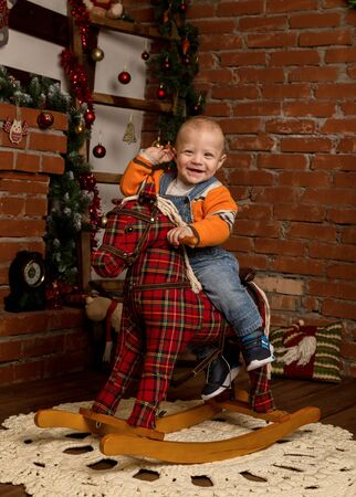 Little baby boy on rocking horse, dressed in sweater and jeans. Christmas or New Year decorations