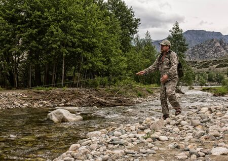 single fisherman on a stormy river is fishing on a sunny summer day
