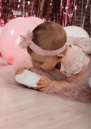 beautiful fashionable little baby in pink dress. little princess poses like a doll