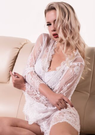 Gentle and seductive blonde woman with attractive body in white lacy lingerie is sitting on sofa. sensual model posing in lace peignoir Reklamní fotografie - 132096423