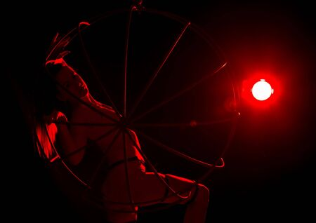 silhouette of dancer woman in red light on a dark background. leggy woman in a bodysuit with metal rings