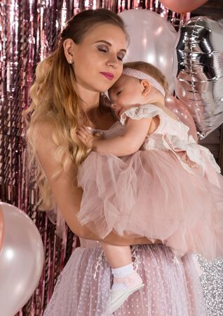 beautiful fashionable little baby in pink dress. little princess poses like a doll with her mam