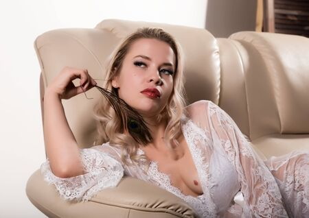 Delicate and beautiful young woman in Lacy white dress lying in sofa and holding a peacock feather