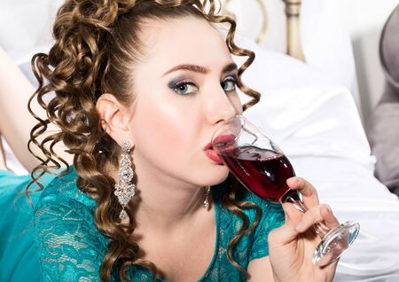 mysterious young curly woman resting on the bed and drinks red wine