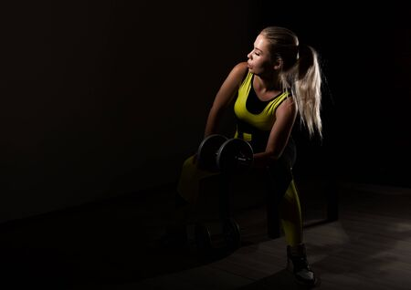 Fitness sexy girl with dumbbells on a dark background. Athlete doing exercises in the gym