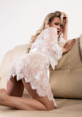 Gentle and seductive blonde woman with attractive body in white lacy lingerie is sitting on sofa. sensual model posing in lace peignoir Standard-Bild