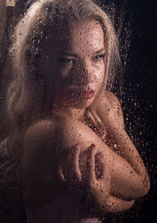 beautyful blonde woman behind wet glass on a dark background, woman takes a shower Standard-Bild