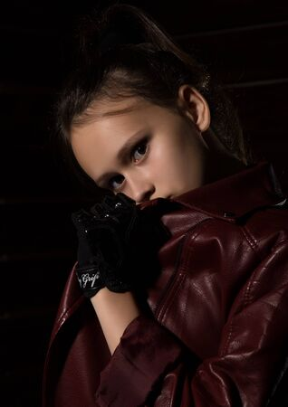 Beautyful Girl in leather jacket in a dark. Mysterious disobedient child, problems with early growing girls Standard-Bild