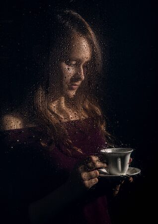 nice young girl drinks coffee behind the wet glass, raindrops on glass Standard-Bild - 142345740