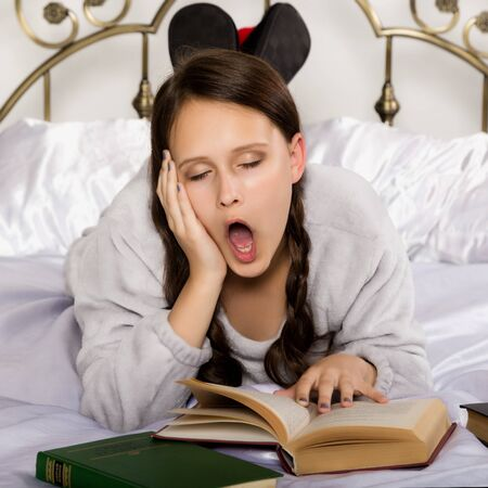 sad young student girl reads a book while lying on a bed doing homework