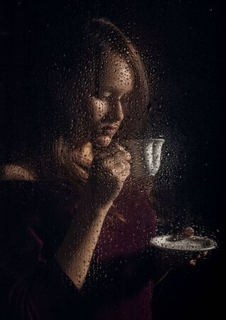 nice young girl drinks coffee behind the wet glass, raindrops on glass Standard-Bild - 142437466