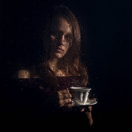 nice young girl drinks coffee behind the wet glass, raindrops on glass Standard-Bild