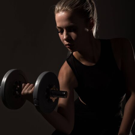 Fitness sexy girl with dumbbells on a dark background. Athlete doing exercises in the gym Standard-Bild - 147881517