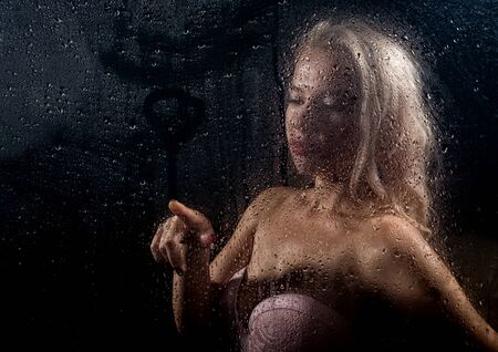 beautyful blonde woman behind wet glass on a dark background, woman takes a shower Standard-Bild - 147881529