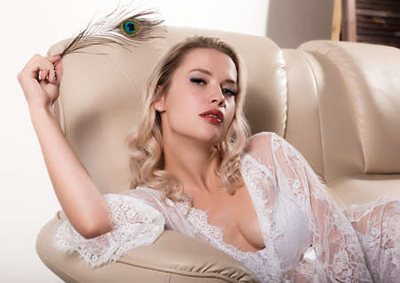 Gentle and seductive blonde woman with attractive body in white lacy lingerie lying on sofa. sensual model posing in lace peignoir Standard-Bild - 152841314