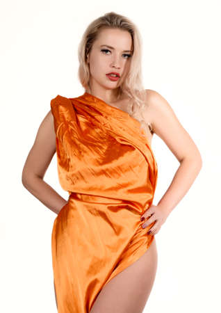 Young stunning tanned blonde woman with long curly hair wearing orange tunic dress posing at camera on a white background. Standard-Bild