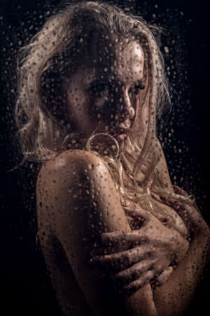 beautyful blonde woman behind wet glass on a dark background, woman takes a shower Standard-Bild - 152841420