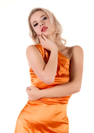 Young stunning tanned blonde woman with long curly hair wearing orange tunic dress posing at camera on a white background. Standard-Bild - 152841421